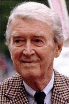 An older James Stewart rocking 1930s-1940s style in the 1990s, with a pinned collar and checked houndstooth jacket.